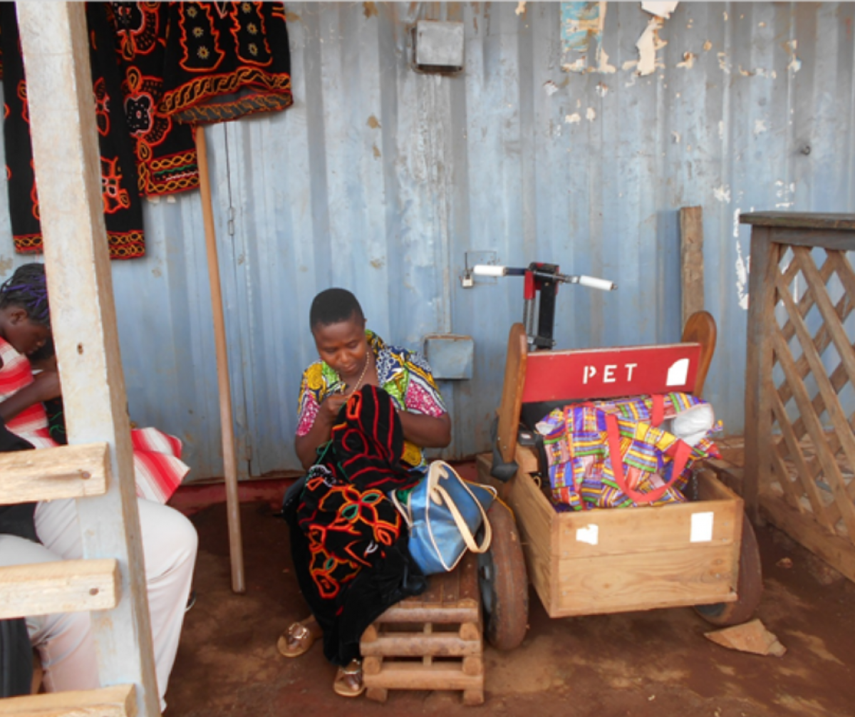 Picture of Nina in front of her shop, embroidering a dress for a customer, copyrigts Cameroon Baptist Convention Health Services