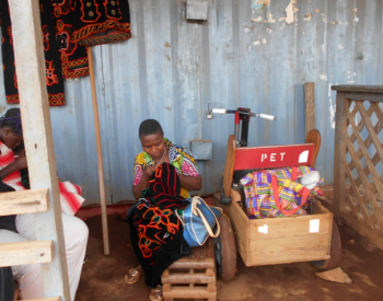 Picture of Nina in front of her shop, embroidering a dress for a customer, copyright Cameroon Baptist Convention Health Services in Cameroon